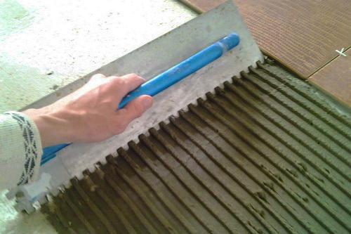 На выровненный пол наносим клеящий раствор и на него выкладываем плитку.