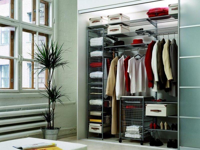 В маленькой гардеробной обязательно нужно разместить вешалки для верхней одежды, корзины для белья и отдел для обуви