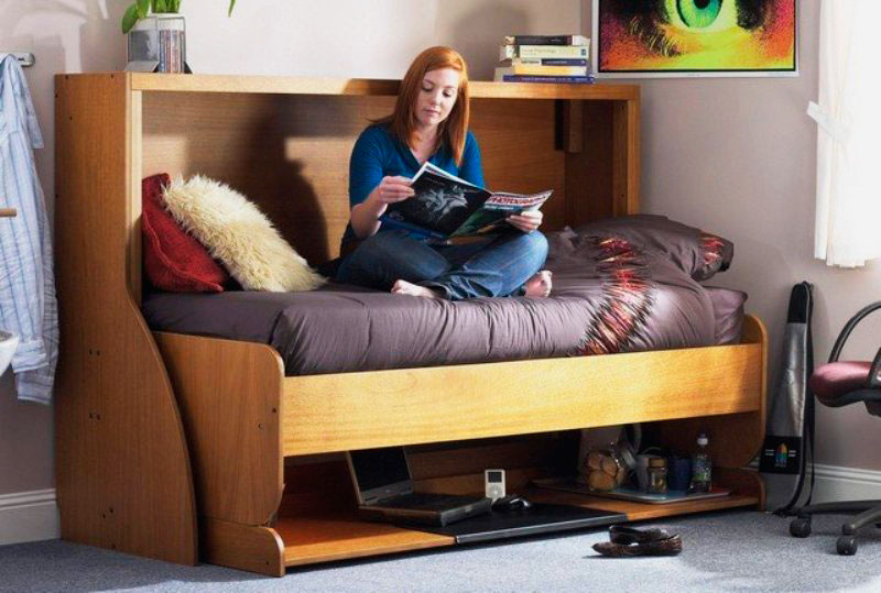 Девочка подросток читает журнал сидя на трансформируемой стол-кровати