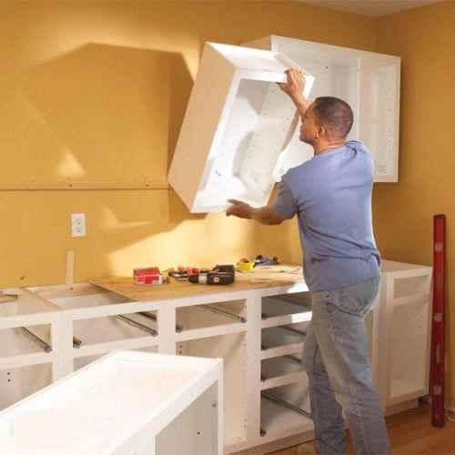 Для более ровной навески можно закрепить временную планку, которая будет являться нижней границей шкафов