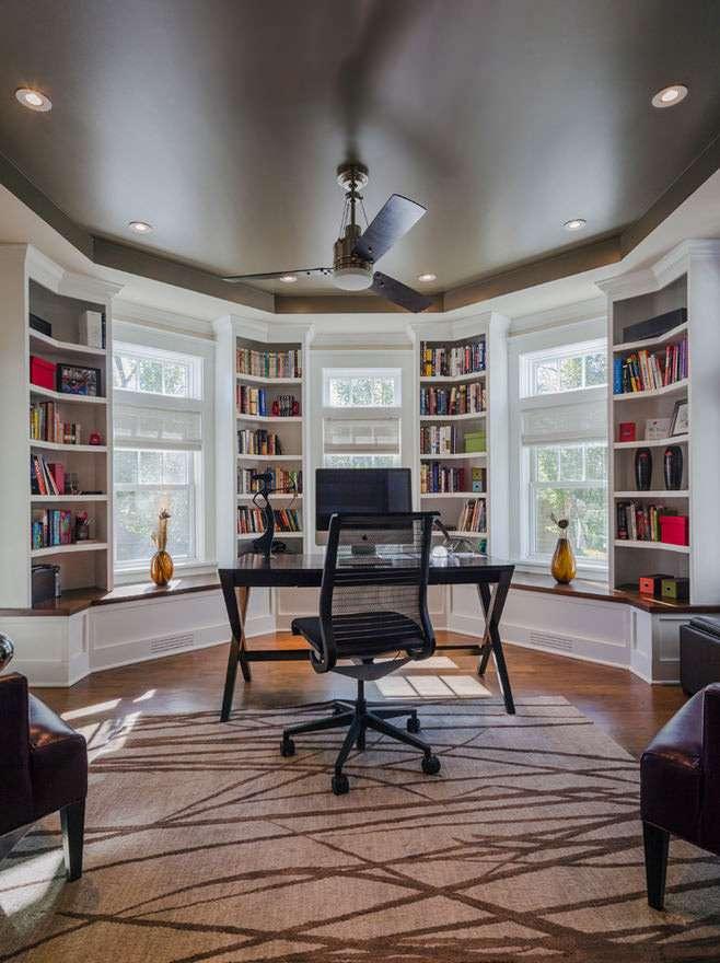 библиотека с рабочим столом в интерьере гостиной с эркером