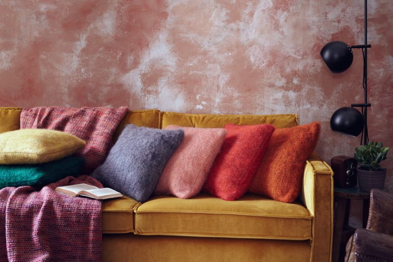 Горчичный диван в гостиной с персиковыми стенами