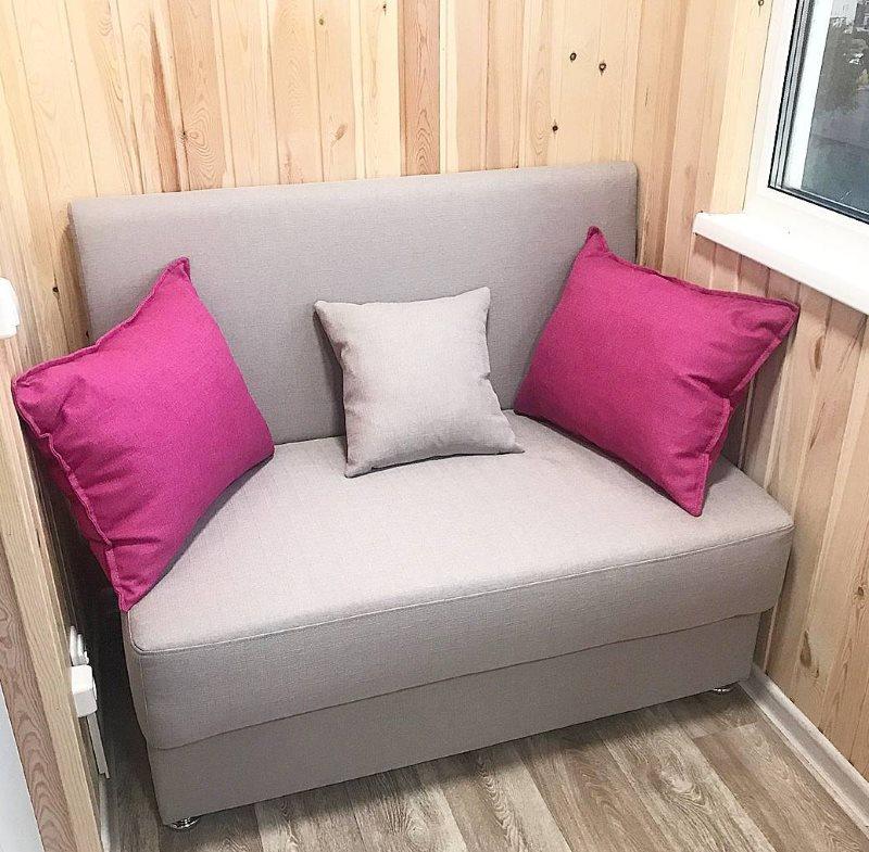 Серый диванчик на балконе с деревянной обивкой