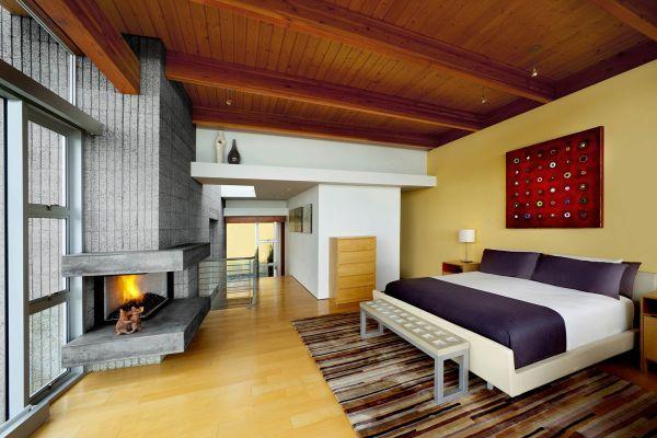 Современное оформление спальни с камином